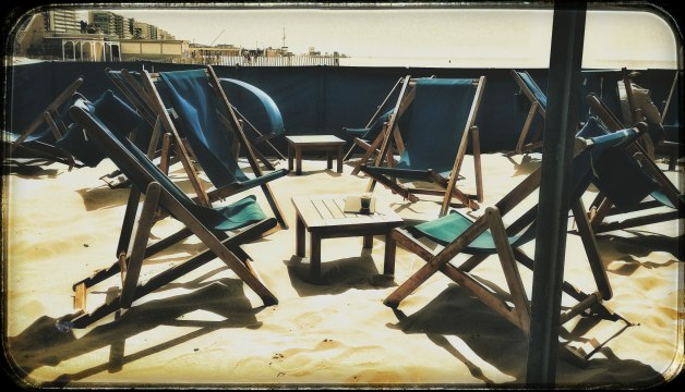 deck chairs on beach with coffee cup